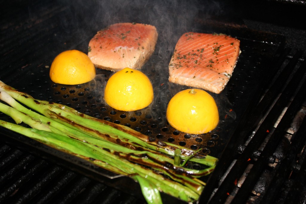 Salmon, lemon halves and green onions on the grill